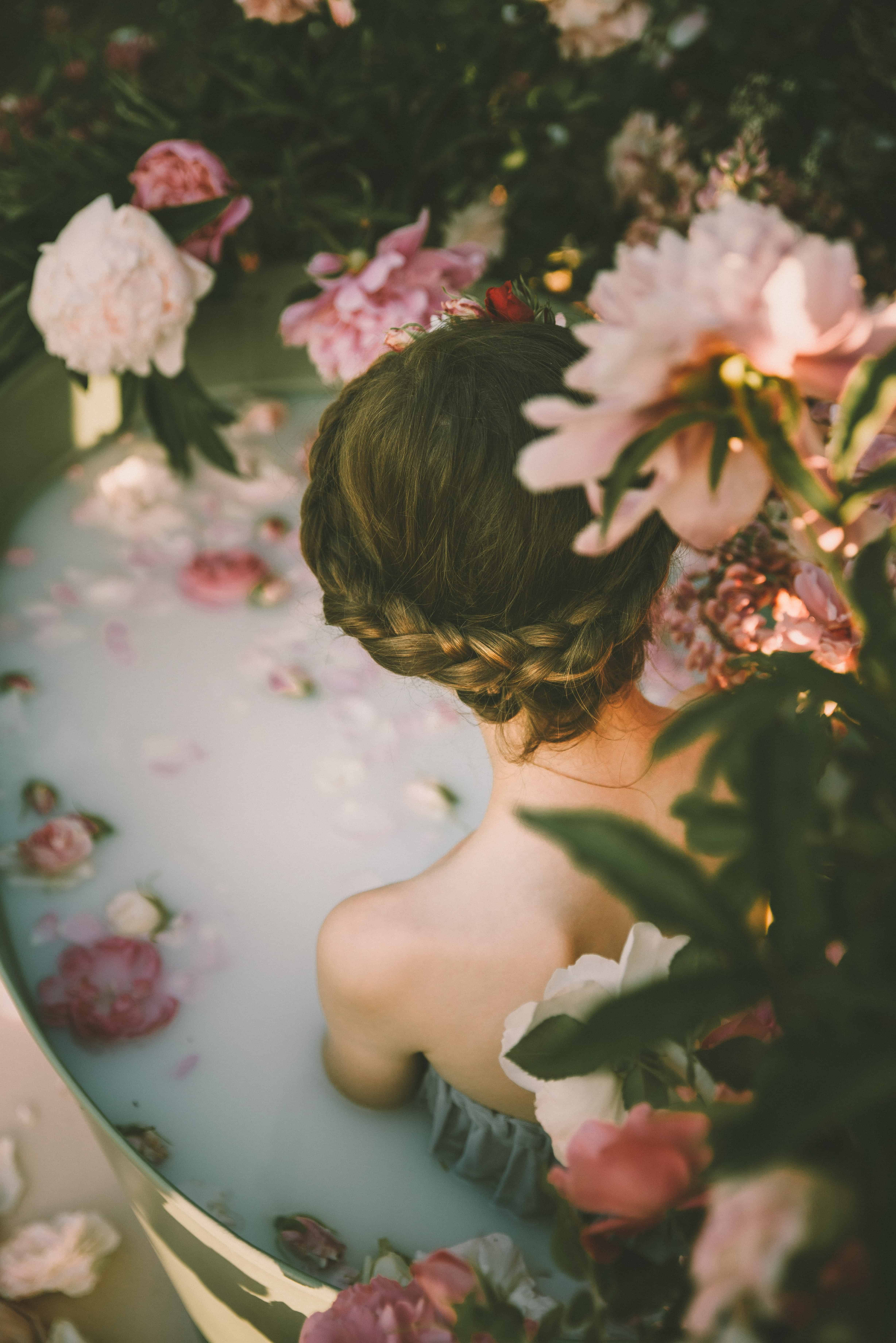Woman in an exotic flower-filled bathtub
